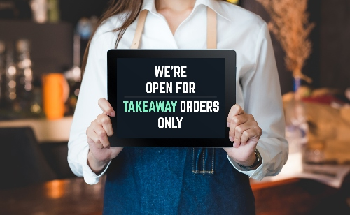 "A server holds a sign that reads ""we're open for takeaway orders only."""